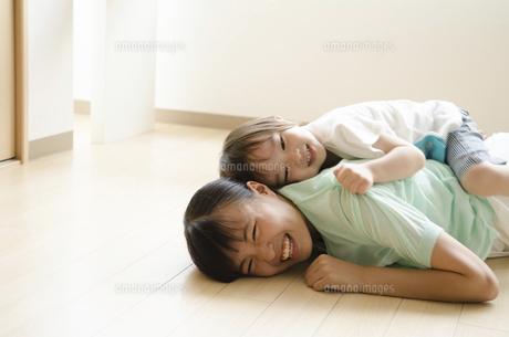 床に転がって笑っている子供たちの写真素材 [FYI01706742]