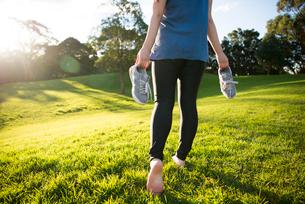 スニーカーを持って裸足で歩いている女性の写真素材 [FYI01706746]