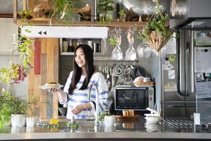 キッチンでお皿を持っている女性の写真素材 [FYI01706749]