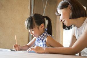 ノートに何か書いている女の子と母親の写真素材 [FYI01706751]