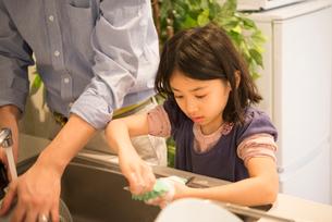 お皿を洗っている女の子と父親の写真素材 [FYI01706756]