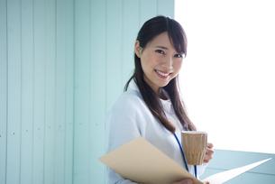 ファイルを開いてカップを持っている女性の写真素材 [FYI01706790]