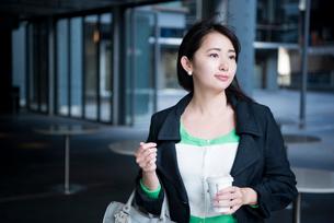 コーヒーを持って遠くをみている女性の写真素材 [FYI01706799]