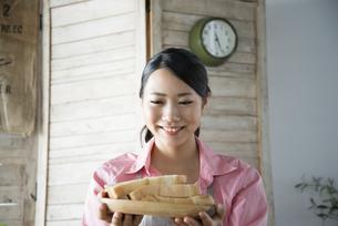 食パンを持って笑っている女性の写真素材 [FYI01706801]