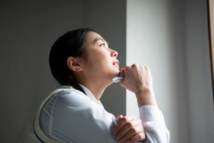 シャープペンシルを持って遠くを見ている女子高生の写真素材 [FYI01706811]