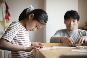 折り紙を折っている女の子と父親の写真素材 [FYI01706822]