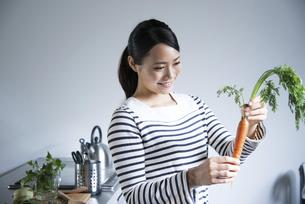 キッチンでにんじんを持っている女性の写真素材 [FYI01706835]