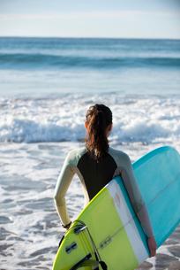 サーフボードを抱えているウェットスーツ姿の女性の写真素材 [FYI01706840]