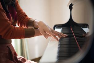 部屋でグランドピアノを弾いている女性の写真素材 [FYI01706848]