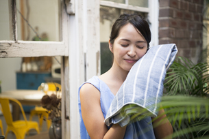 顔をタオルで拭いている女性の写真素材 [FYI01706853]