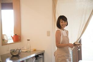 サンドイッチを持って笑っている女性の写真素材 [FYI01706855]
