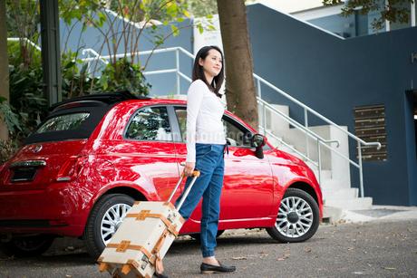 車の前でスーツケースを引いている女性の写真素材 [FYI01706857]