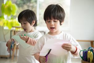 ハサミで遊んでいる双子兄弟の写真素材 [FYI01706875]