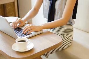 カフェでノートパソコンで仕事をしている女性の手元の写真素材 [FYI01706908]
