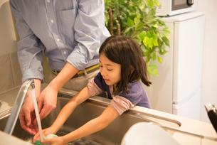 お皿を洗っている女の子と父親の写真素材 [FYI01706918]