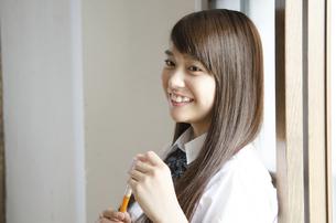 ペンを持って笑っている制服姿の女性の写真素材 [FYI01706924]