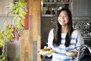 料理の乗ったお皿を持っている女性の写真素材 [FYI01706933]
