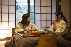 こたつでみかんを食べている浴衣姿の女性2人の写真素材 [FYI01706940]