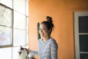 ポットを持って笑っている女性の写真素材 [FYI01706942]