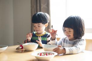 食卓で笑っている兄妹の写真素材 [FYI01706949]