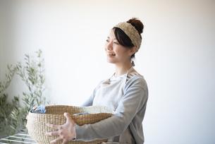 洗濯物の入ったかごを持っている女性の写真素材 [FYI01706967]