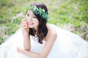 草の上に座るウェディングドレス姿の女性の写真素材 [FYI01706980]