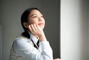 シャープペンシルを持って遠くを見ている女子高生の写真素材 [FYI01706982]