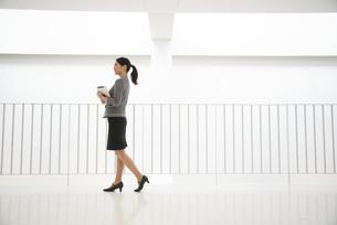 タブレットを抱えて歩いている女性の写真素材 [FYI01706987]