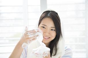 手で泡を作っている女性の写真素材 [FYI01707004]