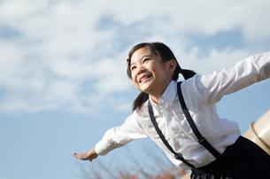飛ぶポーズをしている小学生の女の子の写真素材 [FYI01707033]