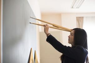 黒板でコンパスを使っている女子高校生の写真素材 [FYI01707052]