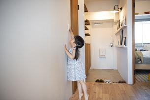 照明のスイッチを触っている女の子の写真素材 [FYI01707078]