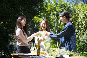 ガーデンパーティで乾杯をしている笑顔の女性3人の写真素材 [FYI01707091]