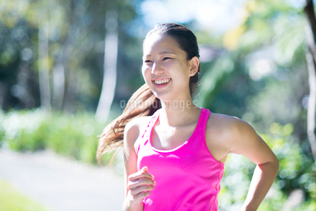 緑の中を走っている女性の写真素材 [FYI01707093]