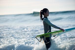 サーフボードを抱えているウェットスーツ姿の女性の写真素材 [FYI01707125]
