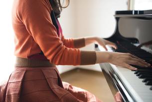 部屋でグランドピアノを弾いている女性の手元の写真素材 [FYI01707136]