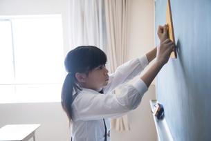 黒板にチョークで線を書く小学生の女の子の写真素材 [FYI01707140]