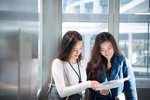 エレベーターの中で打ち合わせをしている女性2人の写真素材 [FYI01707188]