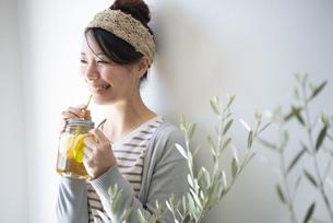 アイスティーを紙ストローで飲んでいる女性の写真素材 [FYI01707223]