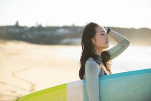 サーフボードを抱えているウェットスーツ姿の女性の写真素材 [FYI01707225]