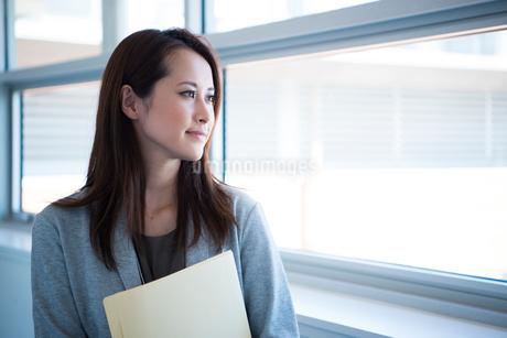 窓をの外を見ている働く女性の写真素材 [FYI01707228]
