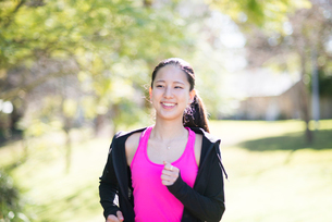 緑の中を笑顔で走っている女性の写真素材 [FYI01707230]