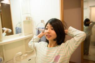 ドライヤーで髪を乾かしている女の子の写真素材 [FYI01707231]