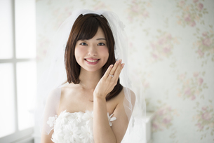 結婚指輪を見せているウェディングドレス姿の女性の写真素材 [FYI01707238]