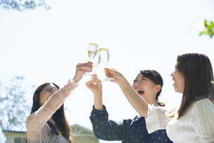 ガーデンパーティで乾杯をしている笑顔の女性3人の写真素材 [FYI01707250]