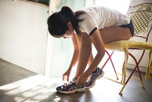 スニーカーの靴紐を結んでいる女性の写真素材 [FYI01707253]