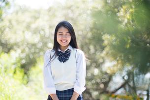 緑の中で笑っている制服姿の女子高生の写真素材 [FYI01707271]