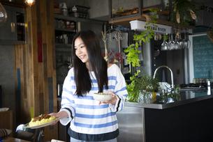 料理の乗ったお皿を持っている女性の写真素材 [FYI01707290]