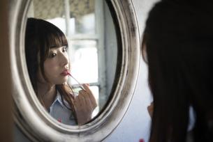 鏡を見ながらグロスを塗っている女性の写真素材 [FYI01707306]