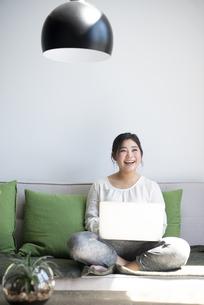 ソファに座ってパソコンを操作しながら笑っている女性の写真素材 [FYI01707331]
